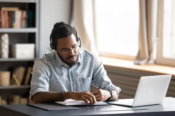 Photo of a man writing notes at a desk with headphones and a laptop